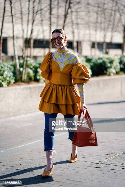 A guest wears sunglasses earrings a yellow and purple floral print turtleneck an orange ruffled gathered dress with puff sleeves ripped hem crop...