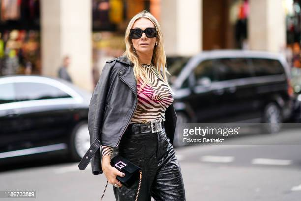 A guest wears sunglasses earrings a zebra pattern print top a black leather jacket a belt blck leather pants a bag outside Giambattista Valli during...