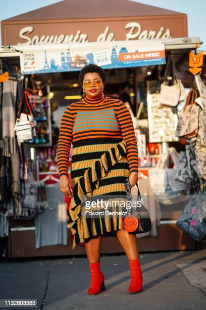 A guest wears sunglasses earrings colorfully striped and ruffle hemmed turtleneck dress a black Kenzo bag red ankle boots outside Rochas during Paris...