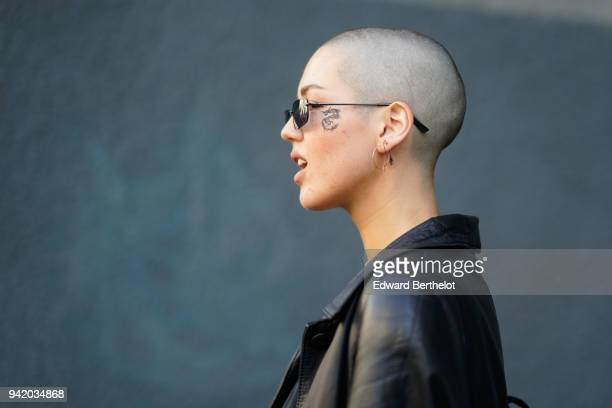 A guest wears sunglasses earrings during London Fashion Week February 2018 on February 16 2018 in London England