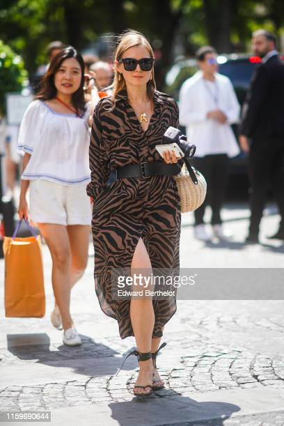 Guest wears sunglasses, earrings, necklaces, a long black and brown zebra pattern shirt-dress, a black belt, a woven bamboo round basket, black ankle...