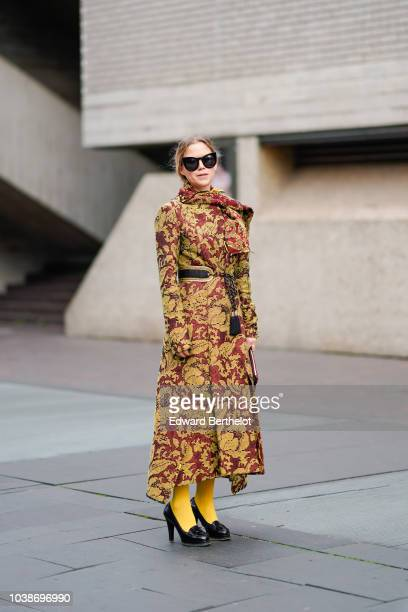 A guest wears sunglasses floral print dress yellow tights black shoes during London Fashion Week September 2018 on September 16 2018 in London England