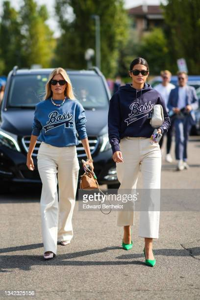 Guest wears sunglasses from Ray Ban, a multicolored pearls bracelet, a gold chain necklace, a blue sweater with Boss embroidered logo from Boss,...