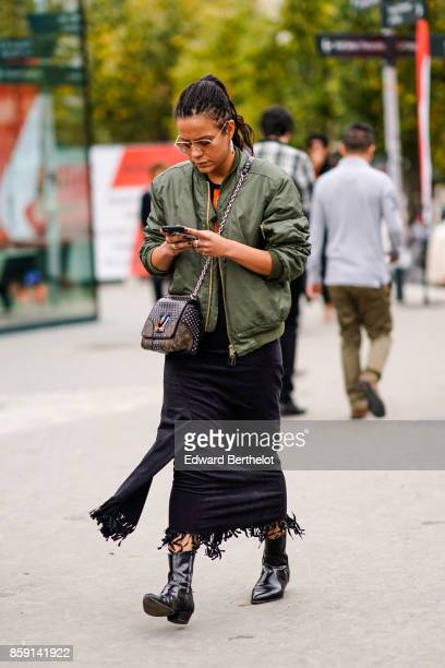 A guest wears sunglasses khaki green bomber jacket LV Vuitton bag black skirt with fringes and black patent leather boots outside Ann Demeulemeester...