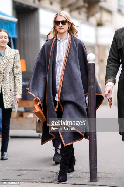 A guest wears sunglasses large creole earrings a striped shirt a tawnylined wrap poncho a tawny handbag black boots during Paris Fashion Week...