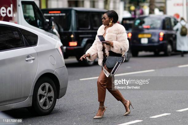 A guest wears sunglasses large earrings a beige fluffy faux fur jacket a grey Christian Dior bag brown leather pants beige pointy highheeled pumps...