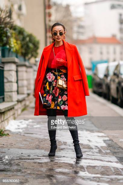 A guest wears sunglasses large earrings a red top aa orange coat a multicolor floral print black Aline skirt black leggings black pointy toe shoes a...