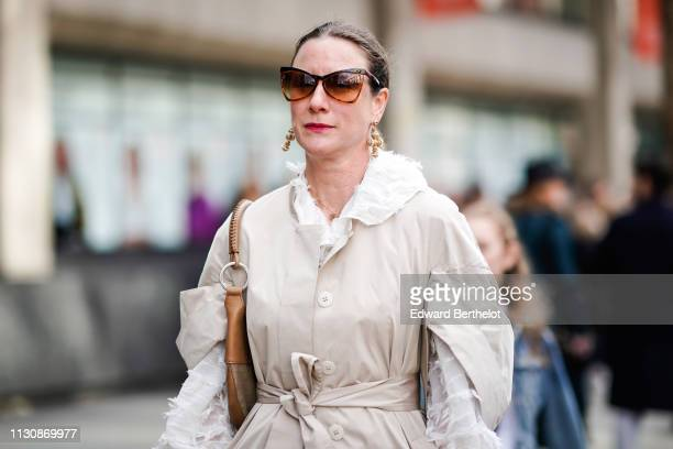 A guest wears sunglasses large earrings a vaporous white shirt a beige trench coat during London Fashion Week February 2019 on February 19 2019 in...