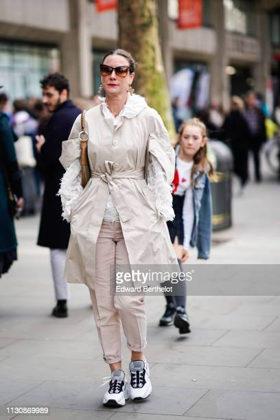 A guest wears sunglasses large earrings a vaporous white shirt a beige trench coat pale pink cuffed pants white and grey sneakers during London...