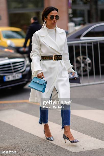 A guest wears sunglasses large earrings a white top a white pagoda sleeves flowy trenchcoat blue denim crop ripped pants a blue handbag a brown...