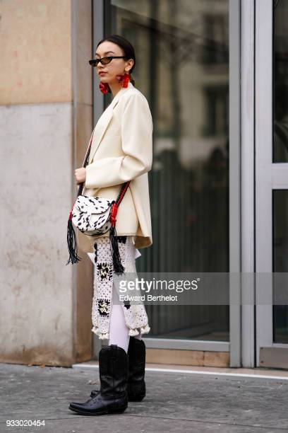 A guest wears sunglasses large red earrings a beige jacket a black and white spotted crossbody bag a tasselslined white crochet skirt with black...