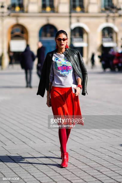 A guest wears sunglasses large red tassels earrings a red bracelet a black leather jacket a white top with colorful pattern a pleated red skirt red...
