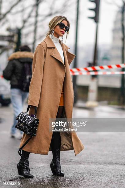 A guest wears sunglasses large silver earrings a white highneck top a camel wrap coat a black quilted Valentino bag black pointy toe chunky heeled...