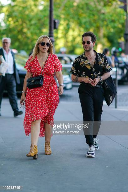 Guest wears sunglasses, necklaces, a black Chanel bag, a wrap-over red hi-lo asymmetric dress with cream-color floral print, mustard-yellow suede...