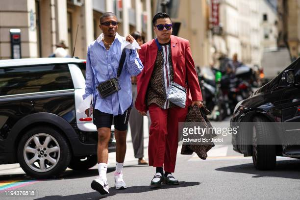 Guest wears sunglasses, necklaces, a blue shirt with white stripes and white collar and cuffs, a metallic caged bag, black cycling shorts, white Nike...
