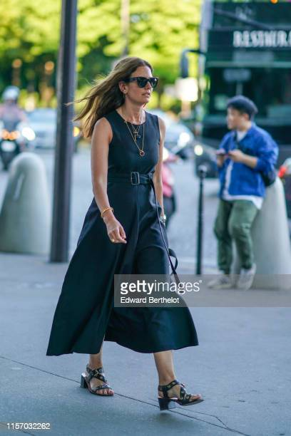 A guest wears sunglasses necklaces a bracelet a black dress black sandals with grommets outside AMI during Paris Fashion Week Menswear Spring/Summer...