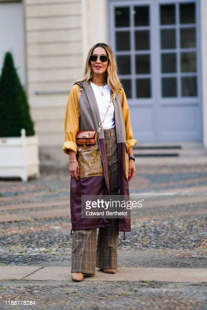 Guest wears sunglasses, necklaces, a white top, a tan-color bag, camel and black Prince of Wales check wide-legs full length pants, a grey and brown...