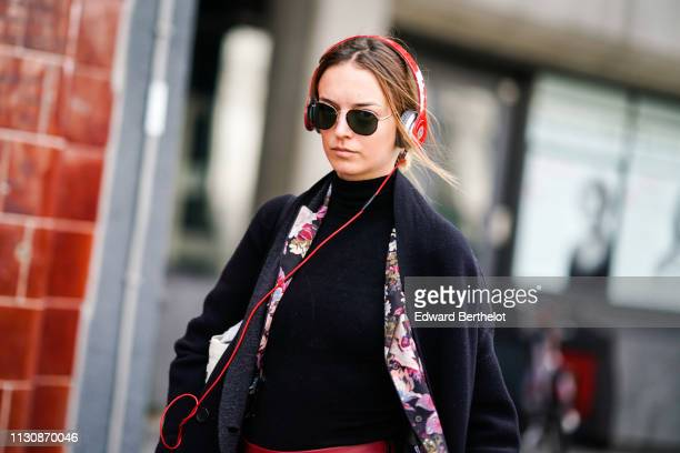 A guest wears sunglasses red headphones from Beats a black turtleneck a floral print jacket a black coat during London Fashion Week February 2019 on...