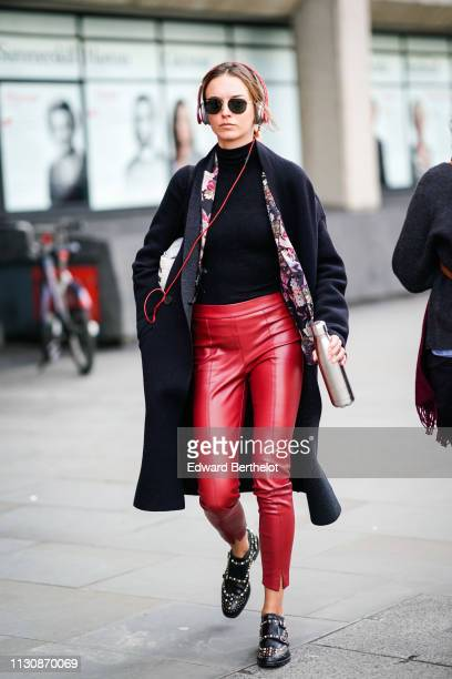 A guest wears sunglasses red headphones from Bose a black turtleneck a floral print jacket a black coat red leather pants black studded shoes during...