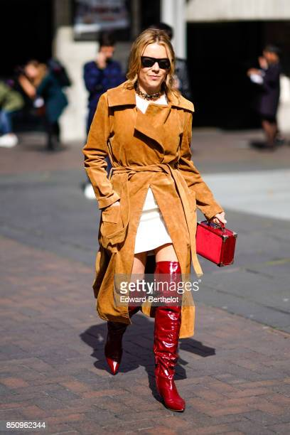 A guest wears sunglasses red thigh high leather boots a red bag a camel trench coat a white dress outside Roland Mouret during London Fashion Week...