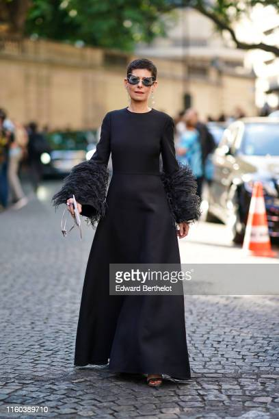 Guest wears sunglasses, star shaped earrings, a black dress with fluffy parts on the sleeves, outside Valentino, during Paris Fashion Week -Haute...