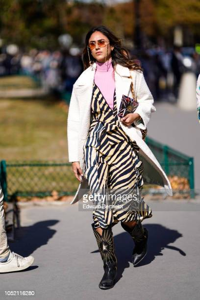 Guest wears sunglasses with chains, a white coat, a pink turtleneck, zebra print striped dress, leather boots, outside Elie Saab, during Paris...