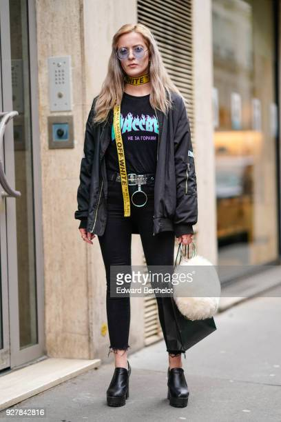 A guest wears transparent sunglasses a yellow offwhite belt as a choker a bomber jacket a tshirt a belt outside APC during Paris Fashion Week...
