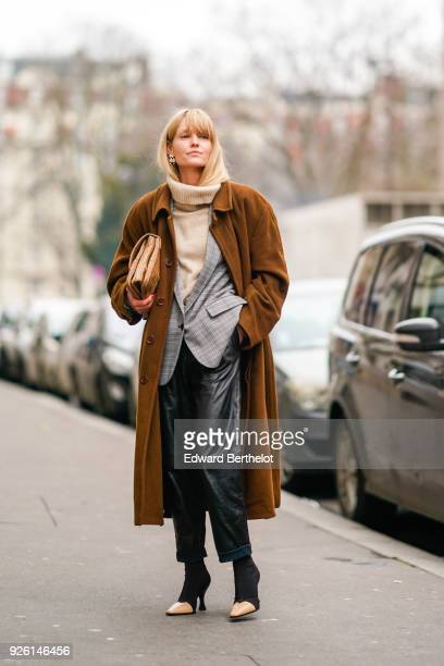 A guest wears turtleneck wool pull over a brown coat black leather pants a gray blazer jacket during Paris Fashion Week Womenswear Fall/Winter...