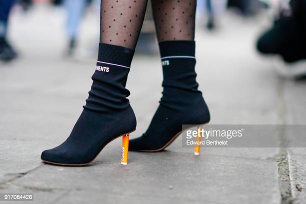 A guest wears Vetements black shoes with orange heels during London Fashion Week Men's January 2018 at on January 6 2018 in London England