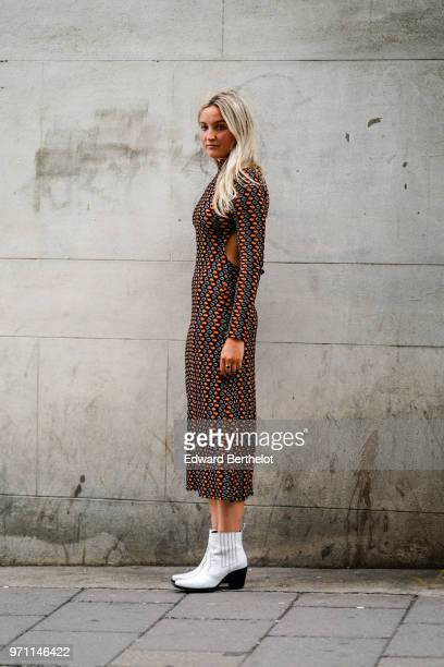 A guest wears white boots a multicolor dress during London Fashion Week Men's June 2018 on June 10 2018 in London England