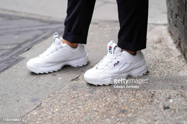A guest wears white FILA sneakers shoes during London Fashion Week Men's June 2019 on June 08 2019 in London England