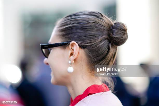 A guest wears white pearl earrings during London Fashion Week February 2018 on February 17 2018 in London England