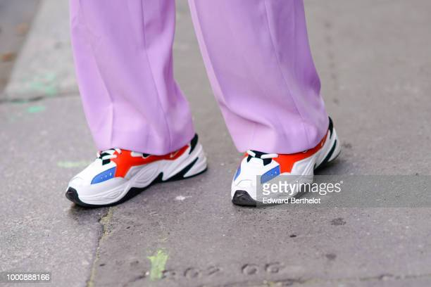 A guest wears white red and blue sneakers shoes outside Thom Browne during Paris Fashion Week Menswear SpringSummer 2019 on June 23 2018 in Paris...
