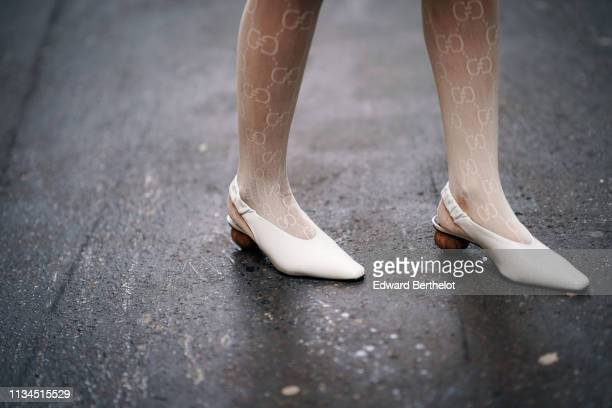 A guest wears white shoes and Gucci tights outside Thom Browne during Paris Fashion Week Womenswear Fall/Winter 2019/2020 on March 03 2019 in Paris...