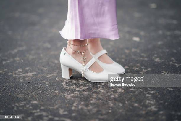 A guest wears white shoes with Chanel ankle jewelry outside Chanel during Paris Fashion Week Womenswear Fall/Winter 2019/2020 on March 05 2019 in...