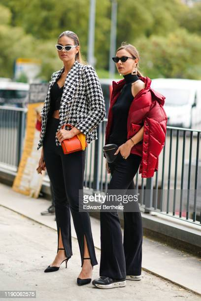 A guest wears white sunglasses a black lace crop top a black and white houndstooth jacket an orange bag black pants black suede pointy heeled...