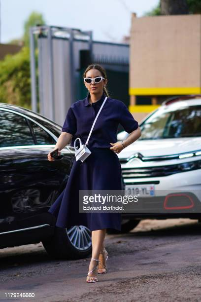 A guest wears white sunglasses a blue dress a white Jacquemus shoulder strapped mini bag outside Lacoste during Paris Fashion Week Womenswear Spring...