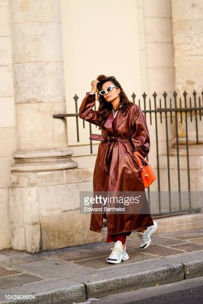 A guest wears white sunglasses a bronze colored trench coat Balenciaga sneakers outside Jacquemus during Paris Fashion Week Womenswear Spring/Summer...