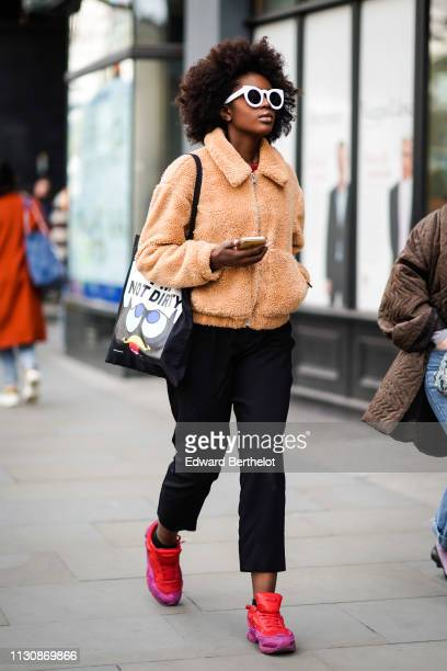 A guest wears white sunglasses a salmon color fluffy jacket black pants red and pink sneakers a tote bag with the impression 'I'm not dirty' during...