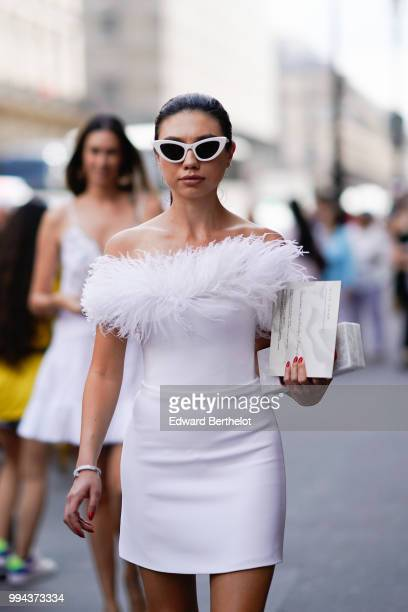 A guest wears white sunglasses a white dress with faux fur outside Elie Saab during Paris Fashion Week Haute Couture Fall Winter 2018/2019 on July 4...