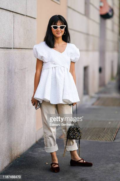 Guest wears white sunglasses, a white embossed fabric gathered V-neck peplum top with puff sleeves, rolled-up hem beige pants, burgundy velvet flat...