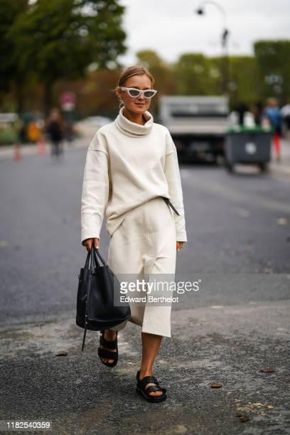 Guest wears white sunglasses, a white front-slit skirt, a white hi-neck top, a black bag, black flat sandals, outside Margiela, during Paris Fashion...