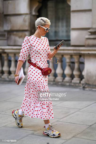 Guest wears white sunglasses, a white pleated dress with red printed polka dots, a red leather Gucci belt bag, Balenciaga sneakers shoes, during...