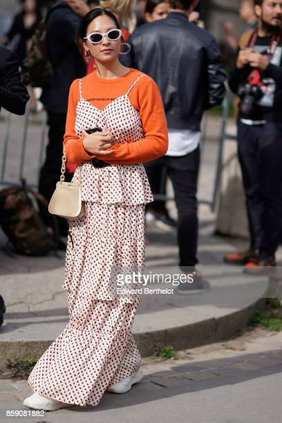 A guest wears white sunglasses an orange top a ruffle dress white sneakers outside Elie Saab during Paris Fashion Week Womenswear Spring/Summer 2018...
