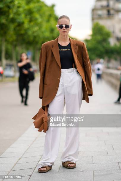 A guest wears white sunglasses an oversized brown blazer jacket a black tshirt white flare pants sandals outside Celine during Paris Fashion Week...
