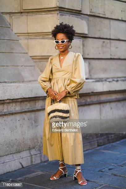 A guest wears white sunglasses earrings a beige dress a fluffy black and white striped bag shoes outside Valentino during Paris Fashion Week Haute...