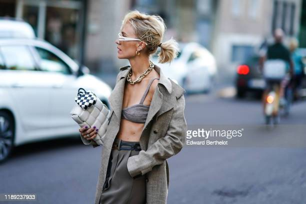 A guest wears white sunglasses hairpins earrings a chain necklace a light grey trench coat a light grey knit bra grey pants a light grey woven...