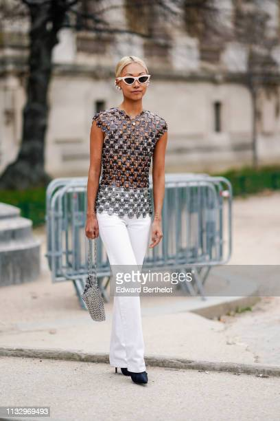 Guest wears white sunglasses, large metallic earrings, a shiny grey transparent vinyl and metal mesh top, white pants, black pointy and high-heeled...