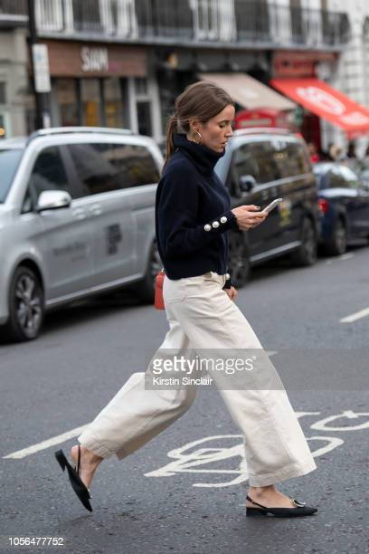 A guest wears white wide legged jeans flat back sling back shoes and a navy blue chunky polo neck sweater during London Fashion Week September 2018...