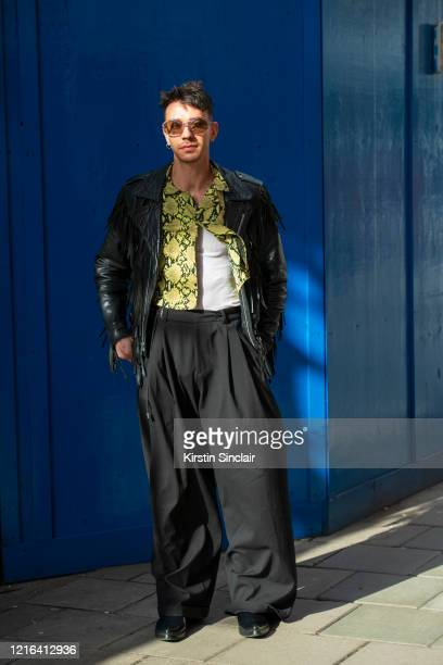 A guest wears wide legged black trousers a black leather jacket and a snakeprint shirt during London Fashion Week February 2020 on February 18 2020...